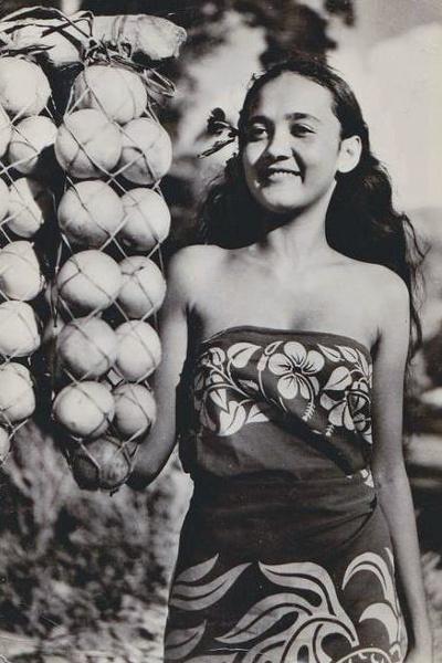 Jeune tahitienne posant à côté de glanes d'oranges du plateau de Tamanu